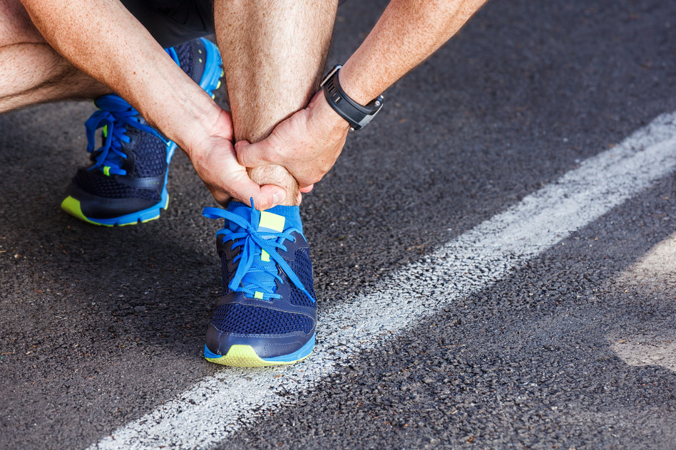 Male runner holding his hurt ankle